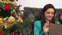 sisters talking on a tablet for a video chat near a Christmas tree