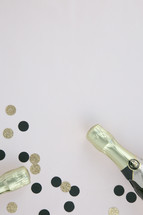 champagne bottles and black and gold confetti