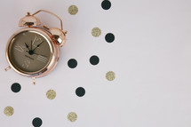 black and gold confetti and alarm clock