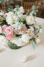 flower arrangement in the center of a table at a wedding reception