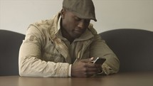 Man sits down and reacts to mobile phone content in an office break room or common area.