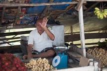 vendor at a market selling potatoes