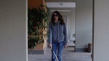 blind woman walking with a walking stick