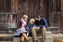 family sitting together on steps outdoors