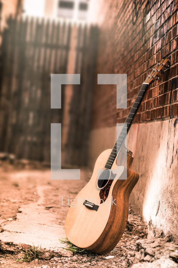 An acoustic guitar in an alley. Guitar. Acoustic guitar. Guitar on wall. Music. Praise and Worship. Acoustic. Guitar Lessons. Tryouts.