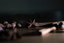 Star Anise, Hazelnuts and Cinnamon on Wooden Board.