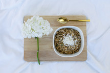 bowl of oatmeal, spoon, and flowers on a wooden tray