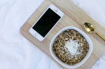 iPhone, bowl of oatmeal, and spoon on a wooden tray