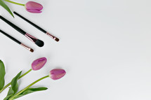 makeup brushes and pink tulips