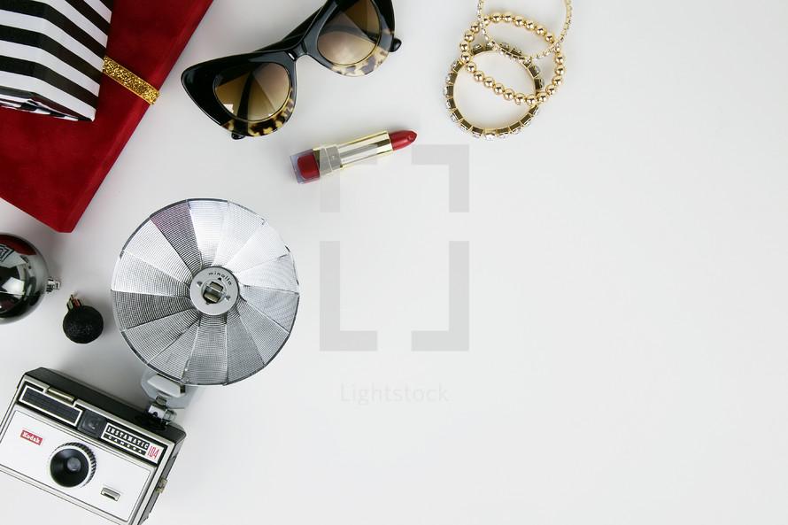 vintage flash camera, lipstick, sunglasses, and Christmas gifts