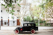 vintage car in front of an historic home