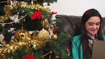 Young happy girls with tablet computer talking online near Christmas tree.