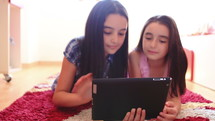 Happy teenager girls having fun using tablet computer at home