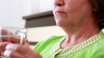 Close up of senior woman taking a pill from nurse