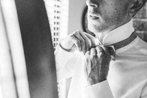 a groom adjusting his bow tie