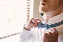 groom adjusting his bow tie