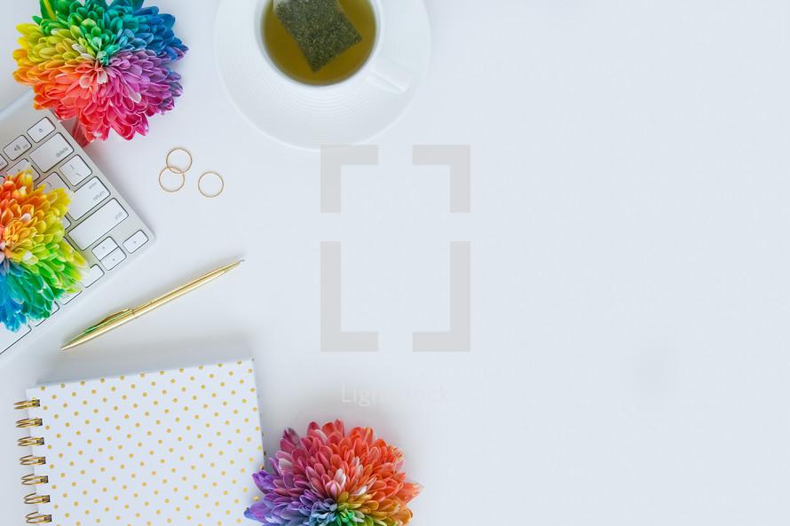 rings, tea, desk, rainbow, flowers, computer, keyboard, pen, gold,  journal, white background