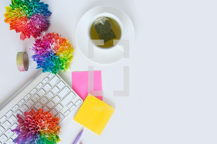 tea bag, notepad, tea, desk, rainbow, flowers, computer, keyboard, pen, gold,  journal, white background