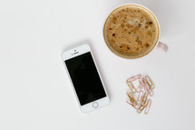 latte in a mug, cellphone and gold paperclips