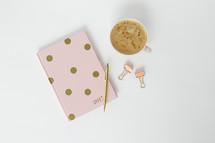latte, pen, polka dot planner, and clips on a desk