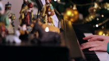 person playing a piano and nativity scene at Christmas