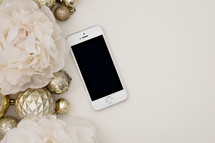 cellphone, gold ornaments and light pink flowers