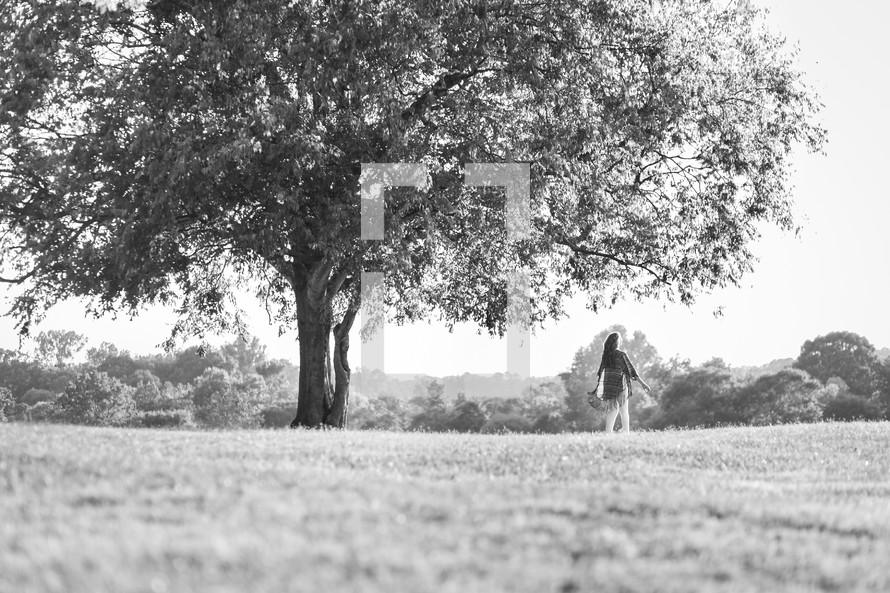 a woman walking under a tree