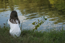 girl looking out at pond water