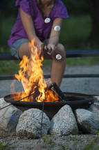 woman roasting marshmallows over a fire