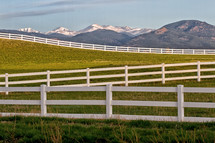 Snow Capped Mountain Peaks and white split rail Fencing