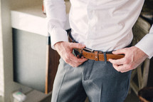 a groom adjusting his belt