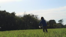 boy child running in a field outdoors