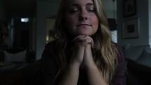 Woman sitting in home praying.