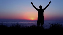 Silhouette of a man raising his hands in worship and praise by the ocean at sunset.