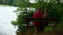 couple sitting on a park bench by a lake