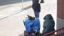 homeless man sitting as pedestrians pass him by