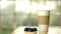 pouring coffee into a paper cup