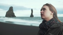a young woman standing on a beach in Iceland looking up