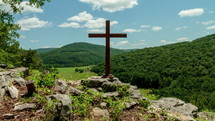 Timelapse of cloud movement over a mountain range and a wooden cross on a hill of rocks.