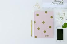 pen, planner, cellphone, calendar, clips, and flowers