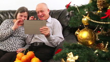 Elderly couple talking near a Christmas tree and using a tablet
