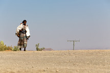 woman walking across a desert