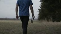 a man walking carrying a Bible