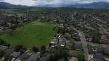 Aerial Shot Flying Over Suburban Neighborhood with Rainclouds in the Distance