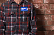 a torso of a man in a plaid shirt with a name tag that reads love
