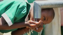 girl drinking water from a well