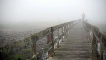 a man walking down a boardwalk on a foggy morning