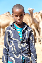 boy in Africa standing with camels