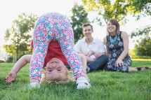 young family sitting in the grass