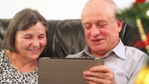 Elderly couple talking near a Christmas tree and using a digital tablet